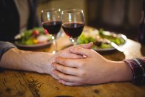 Couple holding hands on table with wine at home — Stock Photo
