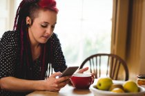 Young woman using phone while sitting at table in home — Stock Photo