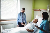 Doctor and nurse interacting with patient in hospital — Stock Photo