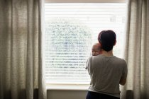Back view of Mother holding her little baby and looking through window at home — Stock Photo