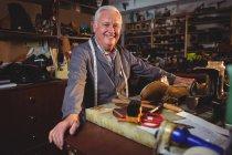 Старший улыбающийся сапожник, стоящий в мастерской — стоковое фото