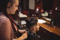 Peluquero femenino quitando delantal de cliente en peluquería - foto de stock