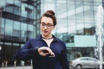 Imprenditrice che controlla il tempo fuori dall'edificio per uffici — Foto stock