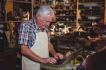 Shoemaker using laptop in workshop interior — Stock Photo