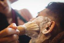 Foco seletivo do homem recebendo sua barba raspada com escova de barbear na barbearia — Fotografia de Stock