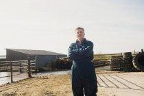 Ritratto di lavoratore agricolo fiducioso in piedi sul campo contro il cielo — Foto stock