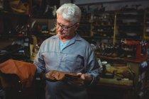 Зрелый сапожник осматривает сапог и кусок материала в мастерской — стоковое фото