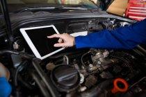 Abgeschnittenes Bild des Mechanikers mit digitalem Tablet bei der Wartung des Automotors — Stockfoto