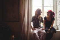 Smiling young couple sitting against window at home — Stock Photo
