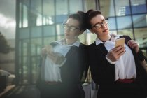 Young businesswoman using mobile phone reflecting on glass while leaning — Stock Photo