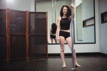 Retrato de pole dancer holding pole en gimnasio - foto de stock