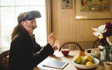 Heureux hipster profiter tout en utilisant le simulateur de réalité virtuelle à la maison — Photo de stock