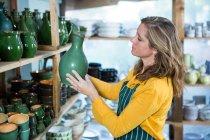 Жіночий Поттер розміщення горщик на полиці в гончарної майстерні — стокове фото