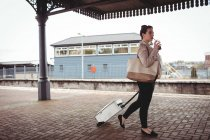 Full length of young woman carrying suitcase at railroad station platform — Stock Photo