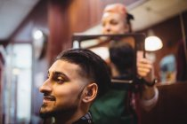 Female barber showing man his haircut in mirror at barber shop — Stock Photo