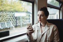 Жінка за допомогою мобільного телефону, сидячи в поїзді — стокове фото