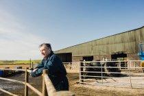 Працівник ферми, спираючись на огорожі на сарай проти неба — стокове фото