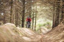 Homme VTT équitation sur le chemin de terre par les arbres dans la forêt — Photo de stock