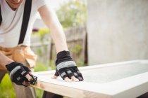 Mittelteil des Tischlers nivelliert Holzrahmen mit Blockebene — Stockfoto