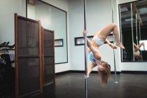 Pole dancer practicing pole dance in fitness studio — Stock Photo