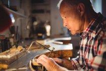 Внимательный ювелир, формирующий металл с помощью пилы в мастерской — стоковое фото