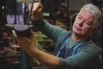 Shoemaker hammering on a shoe in workshop — Stock Photo