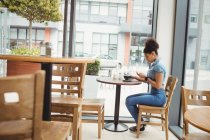 Full length of woman using phone while sitting at restaurant — Stock Photo