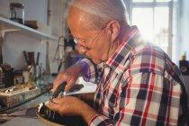Внимательный ювелир с помощью наконечника в мастерской — стоковое фото
