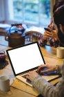 Людина, використовуючи ноутбук на дому за столом з жінкою використовувати смартфон — стокове фото