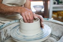 Mid section of potter making pot in pottery workshop — Stock Photo