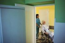 Infermiera che spinge un paziente anziano su una sedia a rotelle in ospedale — Foto stock