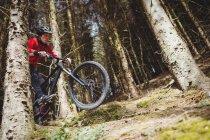 Низкий угол обзора прыжков горных велосипедистов с велосипеда в лесу — стоковое фото