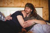 Hipster pareja abrazándose en la cama en casa - foto de stock