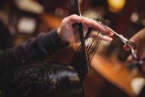Людина стає його волосся з обробкою з ножицями в перукарні — стокове фото