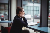 Вид сбоку молодой бизнесвумен, читающей газету в кафе — стоковое фото
