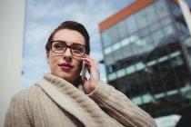 Молодая женщина говорит по телефону по зданию — стоковое фото