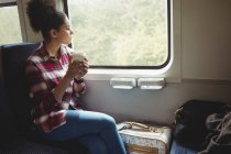 Thoughtful young woman looking through window while having coffee in train — Stock Photo