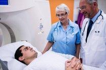 Médicos que interactúan con el paciente en la sala de exploración del hospital - foto de stock