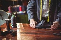 Seção intermediária de sapateiro examinando um sapato na oficina — Fotografia de Stock