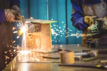 Cropped image of Welders sawing metal with electric worktools and welding in workshop — Stock Photo