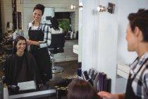 Sorrindo cabeleireiro feminino trabalhando no cliente no salão de cabeleireiro — Fotografia de Stock