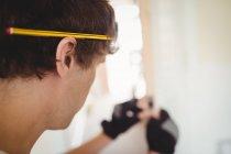 Falegname con la matita sull'orecchio mentre lavora a casa — Foto stock