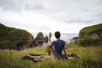 Uomo che effettua yoga sulla scogliera — Foto stock