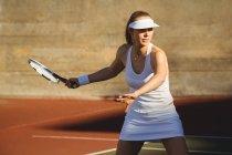 Femme jouant au tennis au tribunal en plein jour — Photo de stock