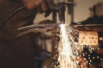 Mid section of blacksmith working at work shop — Stock Photo