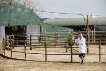 Piena lunghezza del veterinario appoggiato sulla recinzione contro fienile — Foto stock