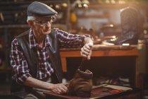 Calzolaio in tappo riparazione di una scarpa in officina — Foto stock