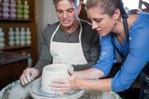 Чоловічий Поттер, допомагаючи жіночий Поттер в гончарні майстерні — стокове фото