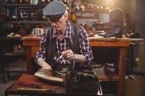 Sapateiro aplicando cola no sapato na oficina — Fotografia de Stock