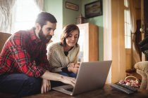 Young couple using laptop in living room at home — Stock Photo